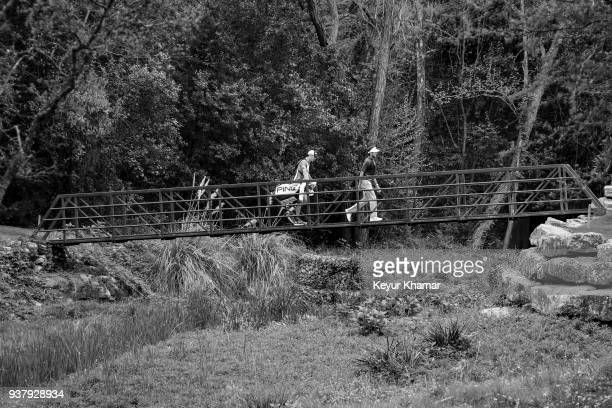 Bubba Watson and his caddie Ted Scott walk across the bridge to the fourth hole green during the championship match at the World Golf...