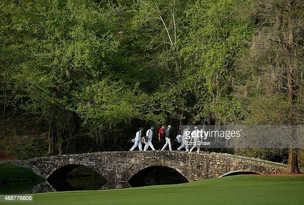 Bubba Watson Brandt Snedeker and Webb Simpson walk across the Nelson Bridge after teeing off on the 13th hole during a practice round at Augusta...