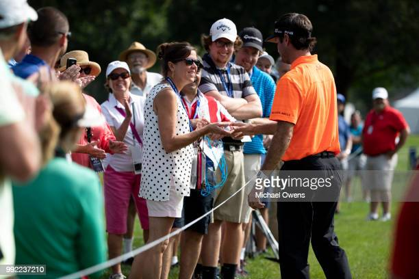 Bubba Watson gives a signed golf ball to a spectator on the 17th hole during round one of A Military Tribute At The Greenbrier at the Old White TPC...