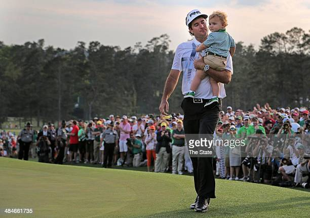Bubba Watson holds his son, Caleb, as he leaves the 18th hole after winning The Masters at Augusta National Golf Club in Augusta, Ga., Sunday, April...
