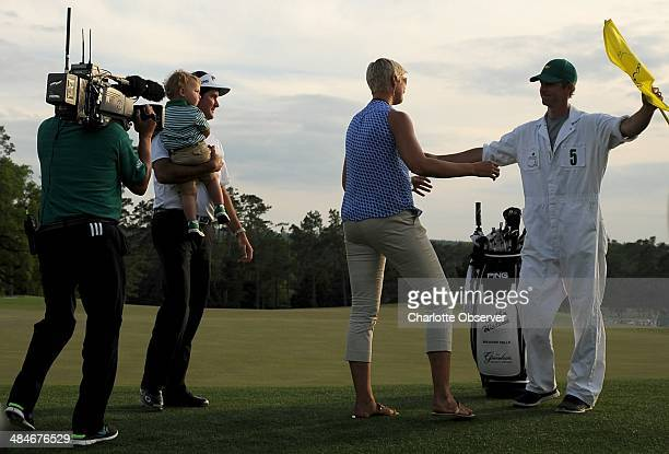 Bubba Watson holds his son Caleb as his wife Angie hugs caddie Ted Scott following The Masters at Augusta National Golf Club in Augusta Ga Sunday...