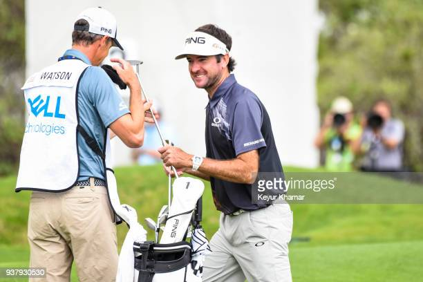 Bubba Watson laughs with his caddie Ted Scott after his chip shot to the 12th hole green during the championship match at the World Golf...