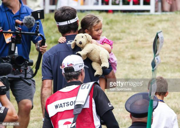 Bubba Watson leaves the course holding his daughter, Dakota, after making a putt for birdie on 18 and ultimately winning the Travelers Championship...