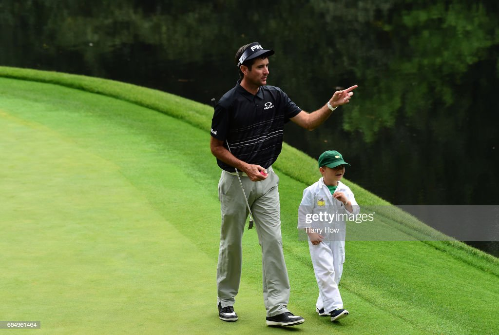 Bubba Watson of the United States and his son Caleb walk during the Par 3 Contest prior to the start of the 2017 Masters Tournament at Augusta National Golf Club on April 5, 2017 in Augusta, Georgia.