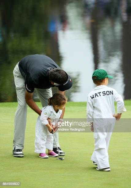 Bubba Watson of the United States helps his daughter Dakota putt as son Caleb looks on during the Par 3 Contest prior to the start of the 2017...