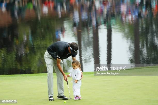 Bubba Watson of the United States helps his daughter Dakota putt during the Par 3 Contest prior to the start of the 2017 Masters Tournament at...