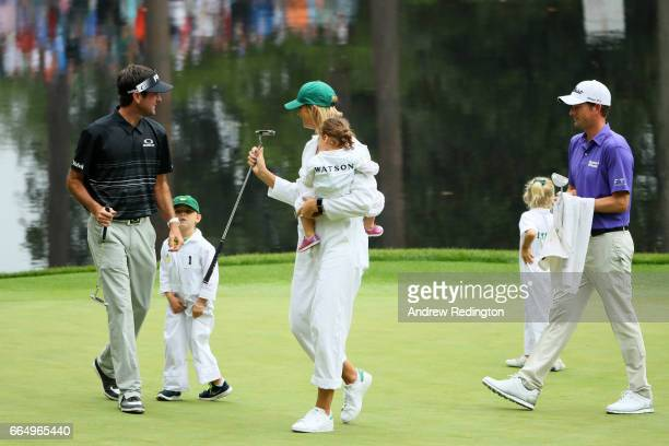 Bubba Watson of the United States his wife Angie and Webb Simpson along with their children react during the Par 3 Contest prior to the start of the...