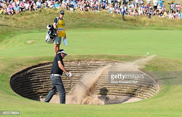Bubba Watson of the United States hits his third shot from a bunker on the 11th hole as caddie Ted Scott looks on during the first round of The 143rd...
