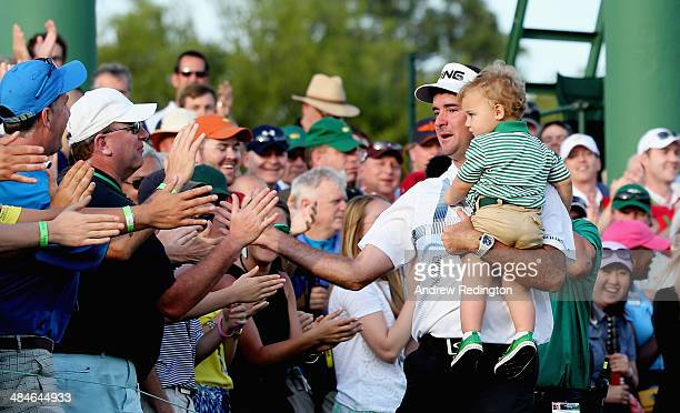 Bubba Watson of the United States holds his son Caleb on the 18th green after winning the 2014 Masters Tournament by a threestroke margin at Augusta...