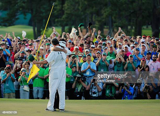 Bubba Watson of the United States hugs his caddie Ted Scott on the 18th green after winning the 2014 Masters Tournament by a threestroke margin at...