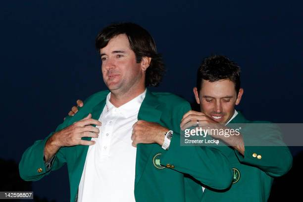 Bubba Watson of the United States is awarded the green jacket by Charl Schwartzel of South Africa during the green jacket presentation after his...