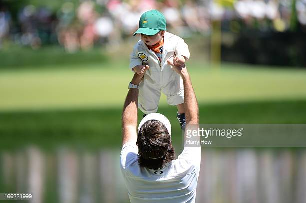 Bubba Watson of the United States lifts his son, Caleb, during the Par 3 Contest prior to the start of the 2013 Masters Tournament at Augusta...