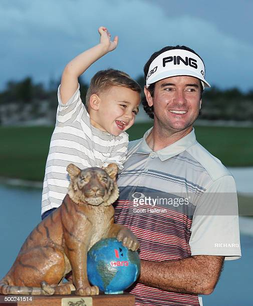 Bubba Watson of the United States poses with his son Caleb and the trophy after his threestroke victory at the Hero World Challenge at Albany The...