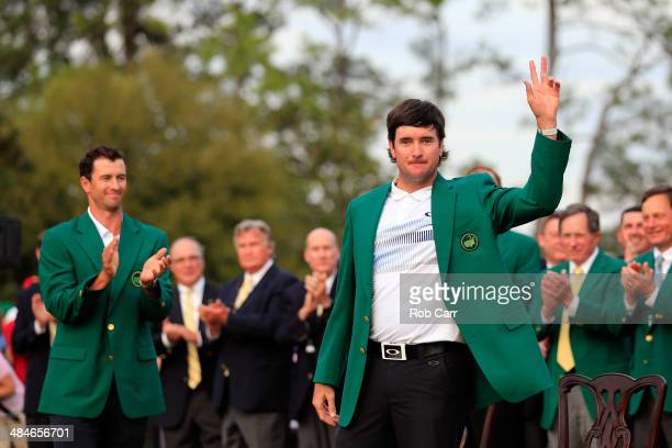 Bubba Watson of the United States poses with the green jacket after winning the 2014 Masters Tournament by a three-stroke margin as Adam Scott of...