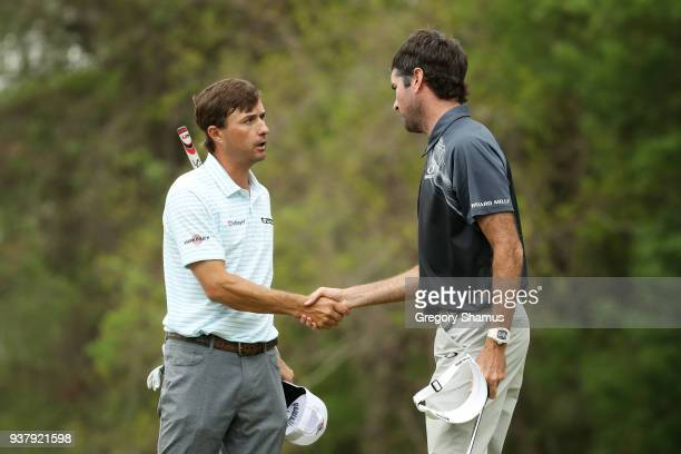 Bubba Watson of the United States shakes hands with Kevin Kisner of the United States after defeating him 76 to win on the 12th green during the...