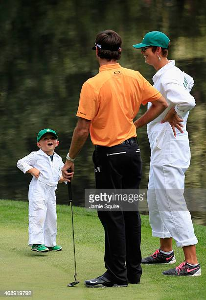 Bubba Watson of the United States waits on a green with his wife Angie and son Caleb during the Par 3 Contest prior to the start of the 2015 Masters...