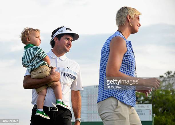 Bubba Watson of the United States waits with his wife Angie and their son Caleb on the 18th green after winning the 2014 Masters Tournament by a...