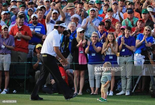 Bubba Watson of the United States walks towards his son Caleb on the 18th green after winning the 2014 Masters Tournament by a threestroke margin at...