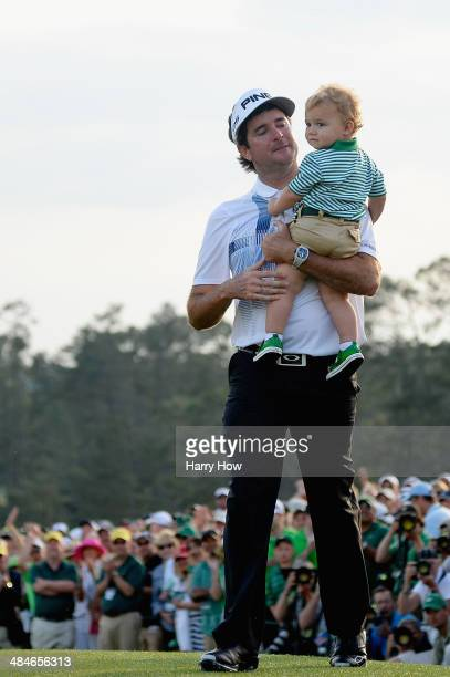 Bubba Watson of the United States walks with his son Caleb off the 18th green after winning the 2014 Masters Tournament by a three-stroke margin at...