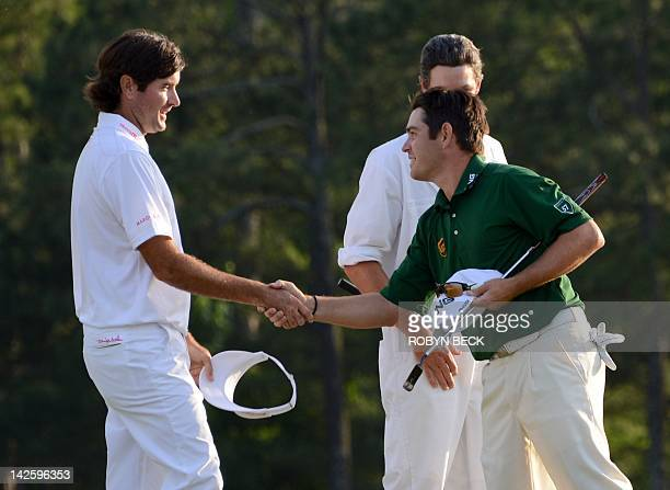 Bubba Watson of the US and Louis Oosthuizen of South Africa shakes after completing the final round of the 76th Masters golf tournament at Augusta...