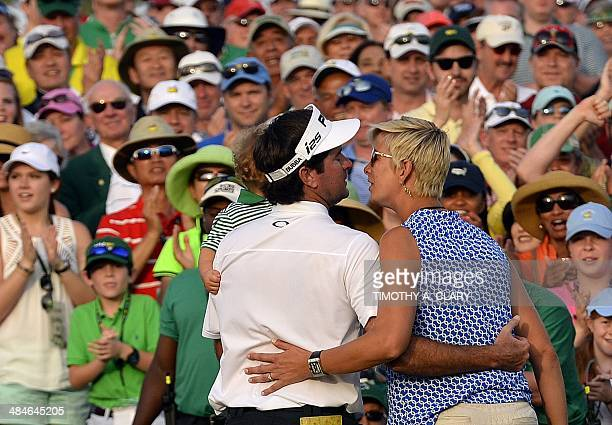 Bubba Watson of the US carries his son Caleb as he kisses his wife Angie after putting on the 18th green during the 78th Masters Golf Tournament at...