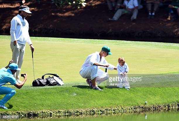 Bubba Watson of the US watches his wife Angie and son Caleb on the 8th green during the Par 3 Contest prior the start of the 78th Masters Golf...
