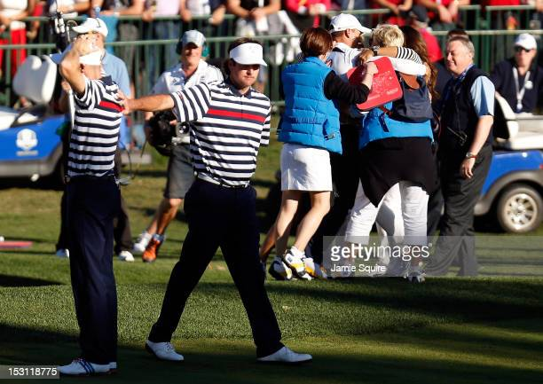 Bubba Watson of the USA conoles Jim Furyk after Furyk missed a par putt on the 18th green during the Singles Matches for The 39th Ryder Cup at...
