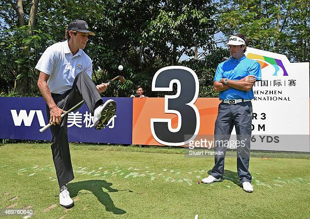 Bubba Watson of USA is entertainted by french trick shot artist and golfer Romain Bechu during the proam prior to the start of the Shenzhen...