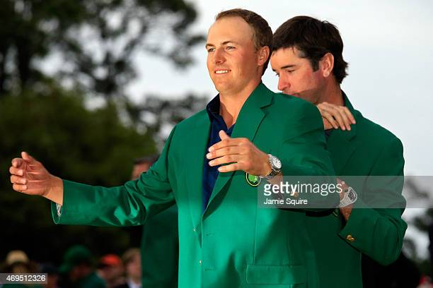 Bubba Watson presents Jordan Spieth of the United States with the green jacket after Spieth won the 2015 Masters Tournament at Augusta National Golf...