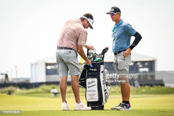 Bubba Watson stands with his caddie Ted Scott on the 18th hole green during practice for the PGA Championship on The Ocean Course at Kiawah Island...