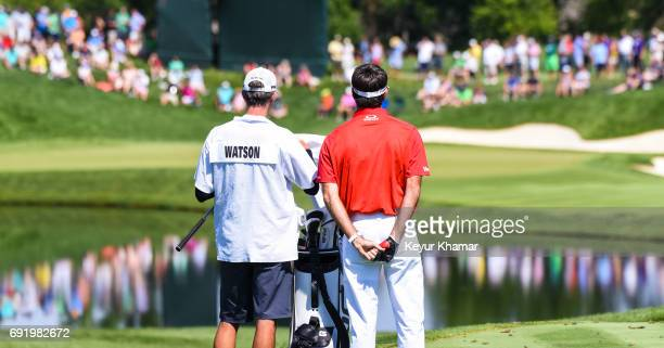 Bubba Watson talks to his caddie Ted Scott after teeing off on the 16th hole during the third round of the Memorial Tournament presented by...
