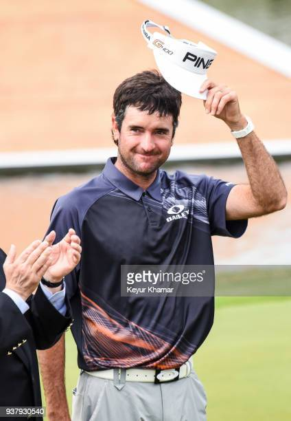 Bubba Watson tips his visor to fans during the trophy ceremony on the 13th hole green following his 76 victory in the championship match at the World...