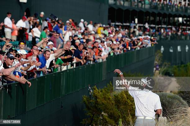Bubba Watson tosses gifts into the crowd on the 16th hole during the first round of the Waste Management Phoenix Open at TPC Scottsdale on January 30...