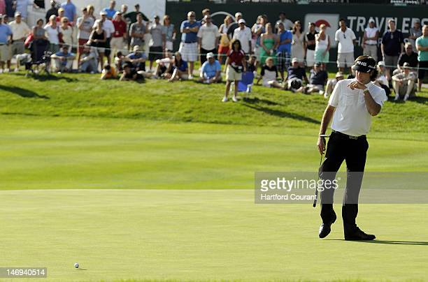 Bubba Watson watches his birdie putt on the 17th hole slip past on the low side during the third round of the 2012 Travelers Championship golf...