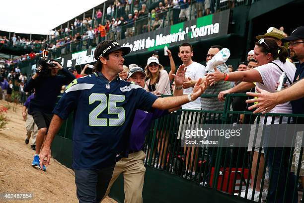 Bubba Watson wears a Seattle Seahawks Richard Sherman jersey while he shakes hands with fans on the 16th fairway during the first round of the Waste...