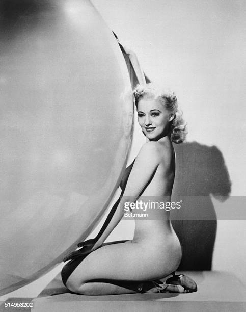 Bubble dancer Sally Rand is shown kneeling and holding large bubble