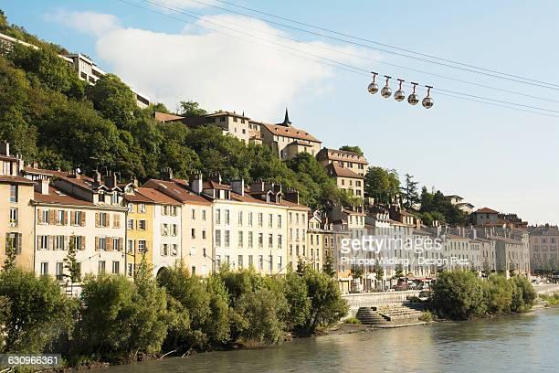 bubble gondola passing over old buildings along a river - grenoble photos et images de collection