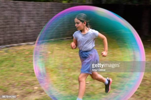 Bubble kid running in backyard.