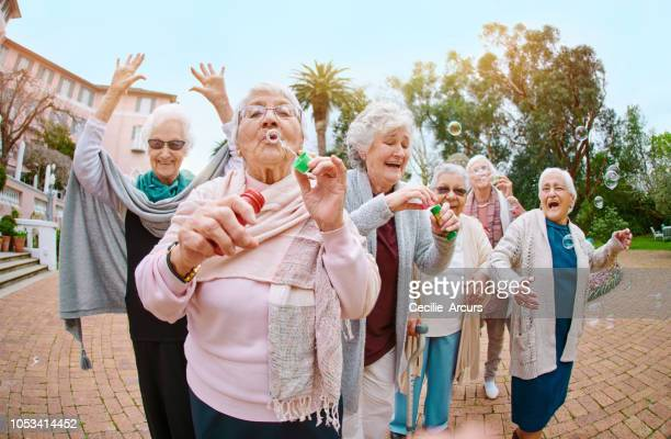 bubbles brings out your inner child! - old lady funny stock pictures, royalty-free photos & images