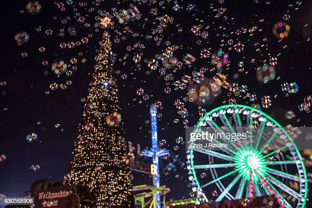 Bubbles fill the air in front of a Christmas tree and ferris wheel at the Winter Wonderland in Hyde Park on December 21 2016 in London England Winter...