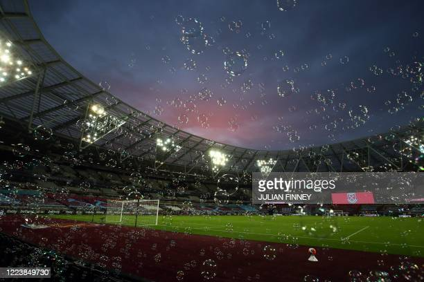 Bubbles float across the pitch at half time of the English Premier League football match between West Ham United and Chelsea at The London Stadium,...