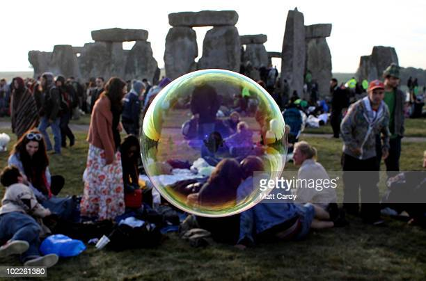 Bubbles float past as revellers watch as the midsummer sun rises just after dawn over the megalithic monument of Stonehenge on June 21 2010 on...
