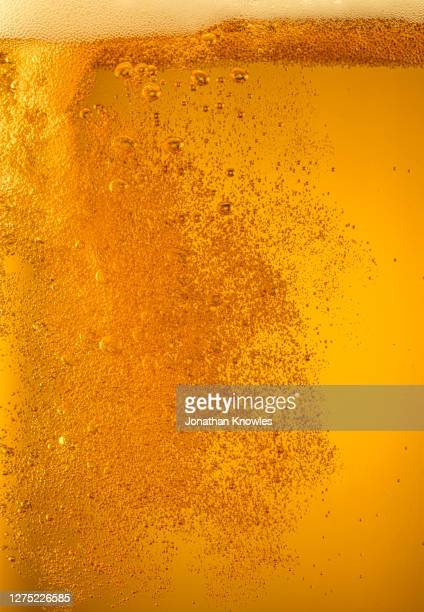 bubbles forming in golden beer - close up stock pictures, royalty-free photos & images