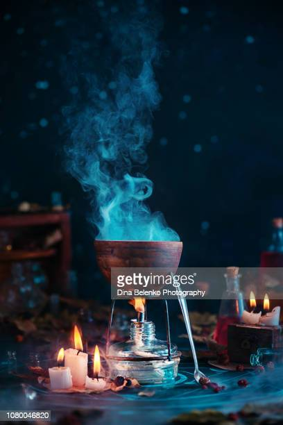 Bubbling and steaming magical potion in a cauldron. Witch or wizard workplace with candle flame and occult items on a dark background with copy space.