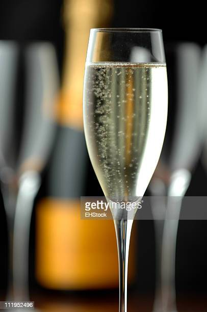 Sprudelnden Champagner Flöten und Flasche auf Schwarz