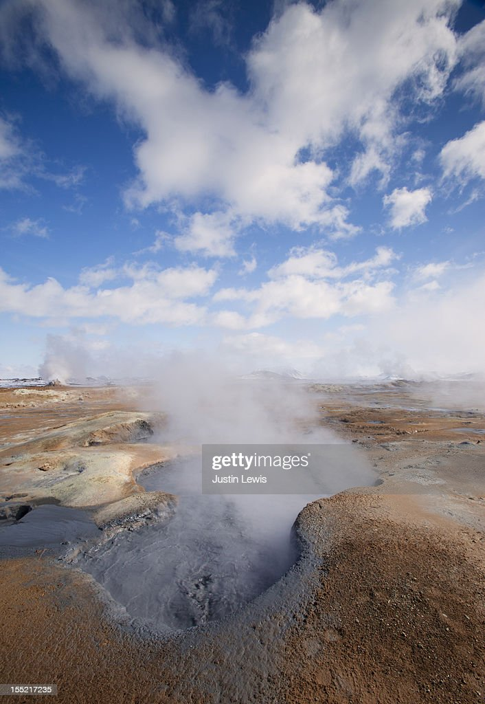 Bubbling geothermal mud pit steams on sunny day : Stock Photo
