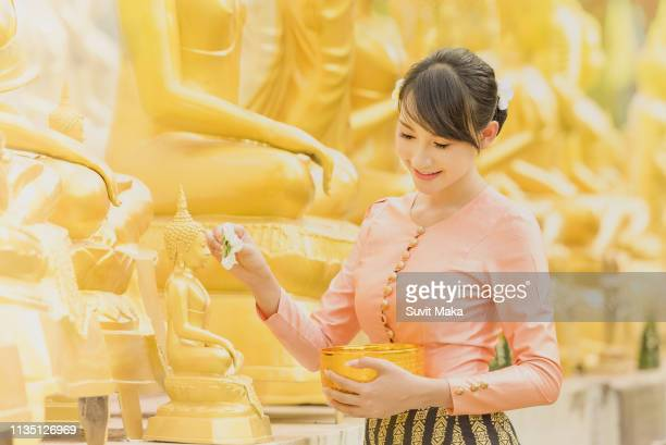 bubuddha statue water ceremony in songkran festival. - buddhist new year stock pictures, royalty-free photos & images