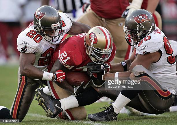 Buccaneers corrnerback Ronde Barber and defensive end Dewayne White try to strip the ball from 49ers rookie running back Frank Gore in the fourth...
