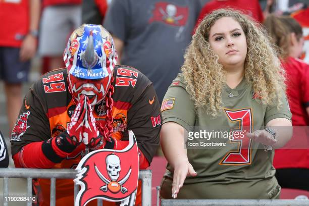 Buccaneers Hall of Fame fan Big Nasty prays as his daughter dances during the regular season game between the Houston Texans and the Tampa Bay...