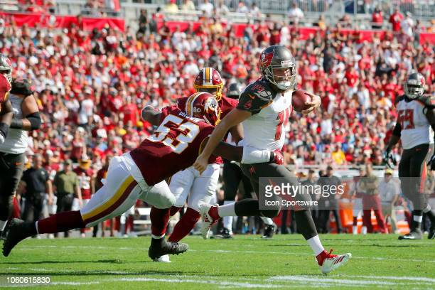 Buccaneers quarterback Ryan Fitzpatrick attempts to get away from Redskins linebacker Zach Brown during the regular season game between the...
